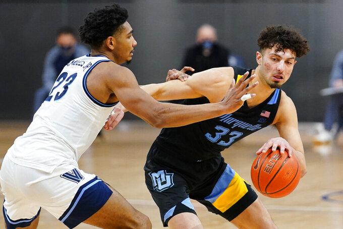 Marquette's Dawson Garcia (33) tries to drive past Villanova's Jermaine Samuels (23) during the second half of an NCAA college basketball game, Wednesday, Feb. 10, 2021, in Villanova, Pa. (AP Photo/Matt Slocum)
