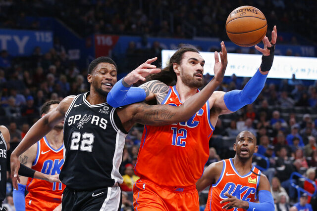 San Antonio Spurs forward Rudy Gay (22) and Oklahoma City Thunder center Steven Adams (12) reach for a rebound in the first half of an NBA basketball game Sunday, Feb. 23, 2020, in Oklahoma City. (AP Photo/Sue Ogrocki)