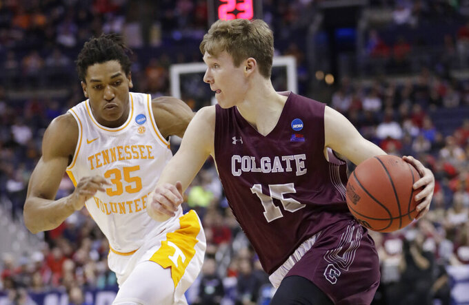 Colgate's Tucker Richardson drives past Tennessee's Yves Pons in the first half of a first-round game in the NCAA men's college basketball tournament in Columbus, Ohio, Friday, March 22, 2019. (AP Photo/Tony Dejak)