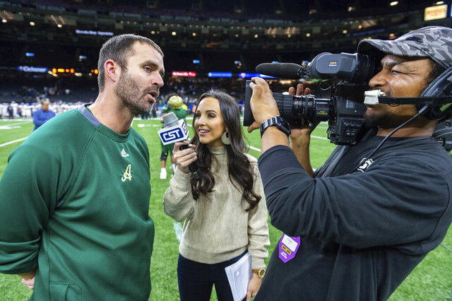 In this Dec. 14, 2019 photo Acadiana head coach Matt McCullough, left, speaks with Carley McCord, center, following a win over the Destrehan in the State Division 5A Championship football game in Lafayette, La. One of victims in a deadly Louisiana plane crash was a sports reporter and daughter-in-law of a Louisiana State University football coach. Steven Ensminger Jr. says his wife, Carley McCord, died in the crash in Louisiana on Saturday, Dec. 28, on the way to a college football playoff game in Atlanta. (Scott Clause/The Daily Advertiser via AP)