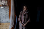 In this Oct. 14, 2019, photo, newly married Kashmiri woman Kulsuma Rameez, 24, stands for photographs inside her home on the outskirts of Srinagar, Indian controlled Kashmir. Kulsuma says she was unable to shop for her wedding and borrowed her wedding dress from a relative. Her ceremony was small, attended by a few relatives and next-door neighbors. After the ceremony, she walked half a kilometer to her new home as the roads were blocked. (AP Photo/ Dar Yasin)