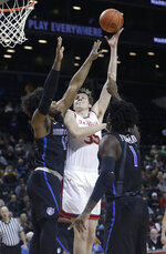 Davidson's Luka Brajkovic (35) shoots over Saint Louis's Hasahn French (11) and D.J. Foreman (1) during the first half of an NCAA college basketball game in the semifinal round of the Atlantic 10 men's tournament Saturday, March 16, 2019, in New York. St. Bonaventure won 68-51. (AP Photo)