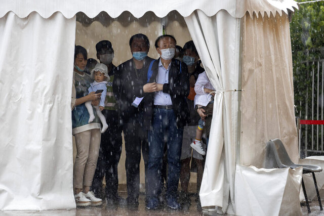 Visitors wearing masks to curb the spread of the coronavirus take shelter from a sudden rainstorm at a park in Beijing on Saturday, May 23, 2020. New coronavirus cases dropped to zero in China for the first time Saturday but overwhelmed hospitals across Latin America – both in countries lax about lockdowns and those lauded for firm, early confinement. (AP Photo/Ng Han Guan)