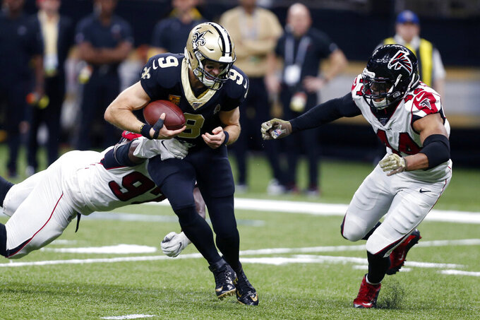 New Orleans Saints quarterback Drew Brees (9) is sacked by Atlanta Falcons defensive tackle Grady Jarrett (97) and defensive end Vic Beasley (44) in the second half of an NFL football game in New Orleans, Sunday, Nov. 10, 2019. (AP Photo/Butch Dill)
