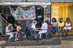 Customers have their nails done near the Baragwanath taxi rank in Soweto, South Africa, Wednesday Sept. 16, 2020. South African president Cyril Ramaphosa is scheduled to address the nation later in the day, as case numbers and death from Covid-19 hit the lowest in months. (AP Photo/Jerome Delay)