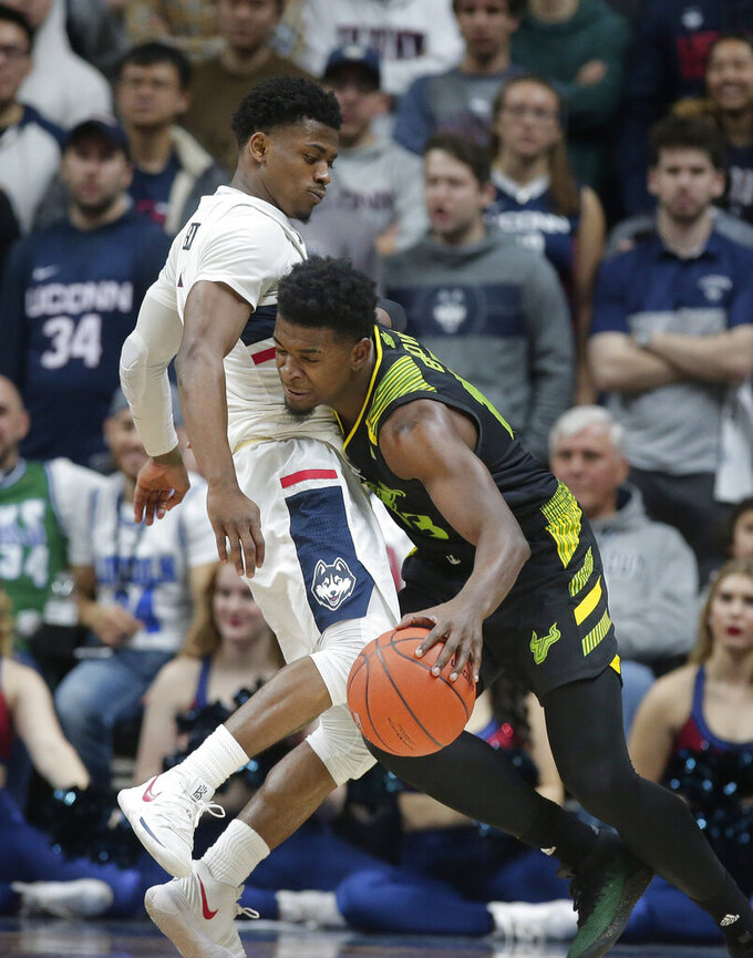Connecticut's Alterique Gilbert, left, tries to block South Florida's Justin Brown, right, during the second half of an NCAA college basketball game, Sunday, March 3, 2019, in Storrs, Conn. (AP Photo/Steven Senne)