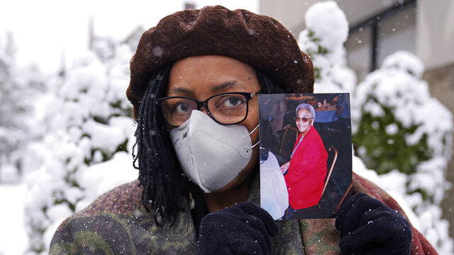 Priscilla Flint-Banks holds a photograph of her 87-year-old mother, Ruby Mae Kinney, who died during April of COVID-19, Friday, Oct. 30, 2020, in the Dorchester neighborhood of Boston. Once a coronavirus hot spot, Massachusetts was seen as a model for infection control this summer as coronavirus cases and deaths dwindled. Now, experts are warning the state could be headed for a bleak winter as its cases climb once again and confirmed deaths surpass 10,000. Massachusetts hit 10,015 confirmed coronavirus deaths on Thursday, Nov. 12, 2020 nearly nine months after the state's initial case was detected. (AP Photo/Charles Krupa)