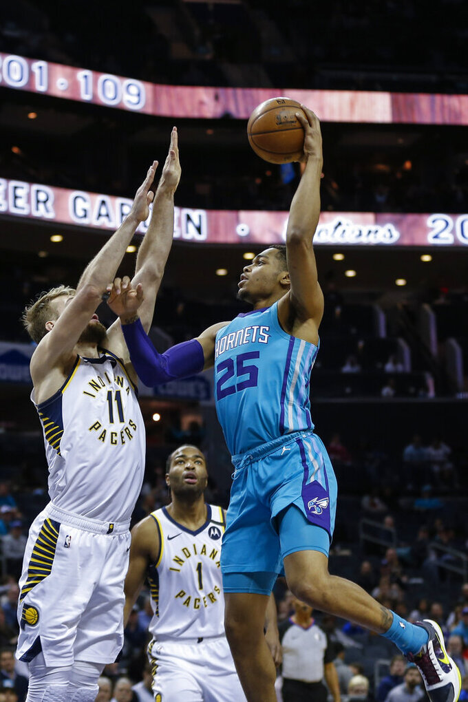 Charlotte Hornets forward P.J. Washington, right, shoots over Indiana Pacers forward Domantas Sabonis in the first half of an NBA basketball game in Charlotte, N.C., Monday, Jan. 6, 2020. (AP Photo/Nell Redmond)