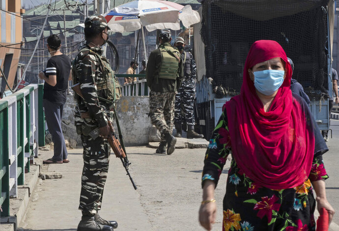 """Indian paramilitary soldiers stand guard in Srinagar, Indian-controlled Kashmir, Saturday, Oct. 3, 2020. Government investigators exhumed the bodies Saturday of three young men in disputed Kashmir, police and victims' families said, two weeks after the Indian military in a rare admission said its soldiers exceeded their legal powers in the killings of the men it had described as """"Pakistani terrorists."""" (AP Photo/Mukhtar Khan)"""