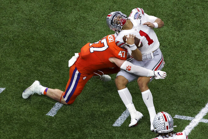 Ohio State quarterback Justin Fields gets hit by Clemson linebacker James Skalski during the first half of the Sugar Bowl NCAA college football game Friday, Jan. 1, 2021, in New Orleans. Skalski was ejected from the game for targeting. (AP Photo/Butch Dill)