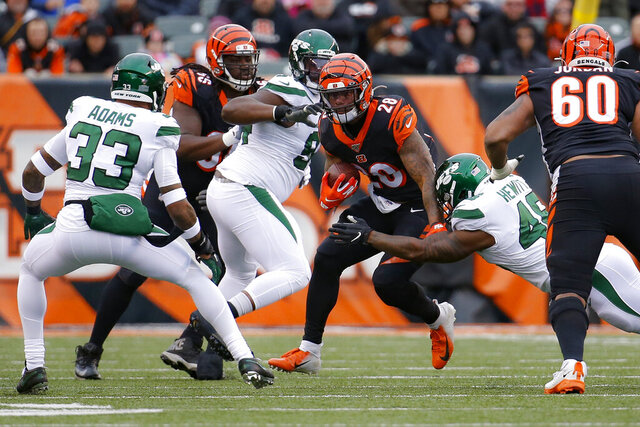 Cincinnati Bengals running back Joe Mixon (28) runs the ball against New York Jets outside linebacker Jordan Jenkins (48) and strong safety Jamal Adams (33) during the first half of an NFL football game, Sunday, Dec. 1, 2019, in Cincinnati. (AP Photo/Frank Victores)