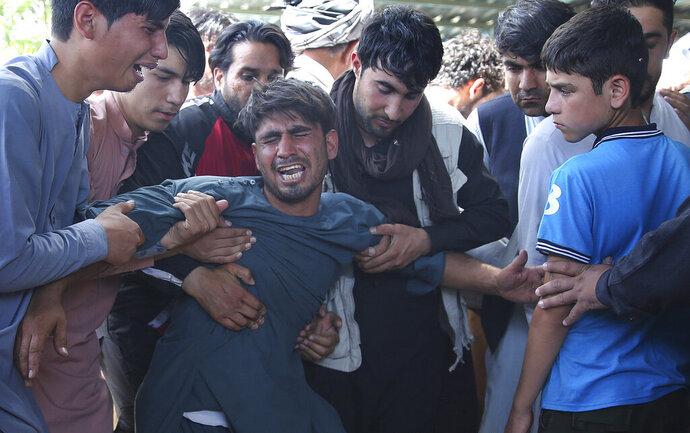 Relatives grieve near the coffins of victims of the Dubai City wedding hall bombing during a mass funeral in Kabul, Afghanistan, Sunday, Aug.18, 2019. The deadly bombing at the wedding in Afghanistan's capital late Saturday that killed dozens of people was a stark reminder that the war-weary country faces daily threats not only from the long-established Taliban but also from a brutal local affiliate of the Islamic State group, which claimed responsibility for the attack. (AP Photo/Rafiq Maqbool)