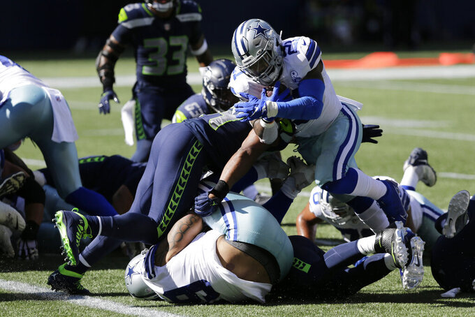 Dallas Cowboys running back Ezekiel Elliott rushes for a touchdown against the Seattle Seahawks during the first half of an NFL football game, Sunday, Sept. 27, 2020, in Seattle. (AP Photo/John Froschauer)