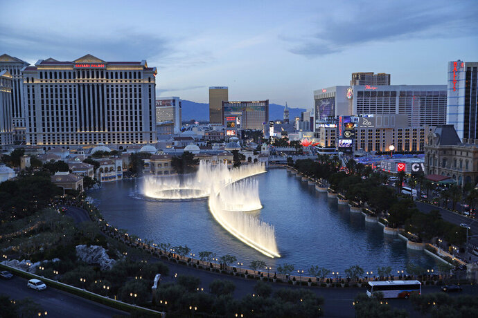 FILE - In this April 4, 2017, file photo, the fountains of Bellagio erupt along the Las Vegas Strip in Las Vegas. MGM Resorts International announced the sale Tuesday, Oct. 15, 2019, of two casinos that will significantly alter its portfolio of Las Vegas Strip properties and offer up cash. (AP Photo/John Locher, File)