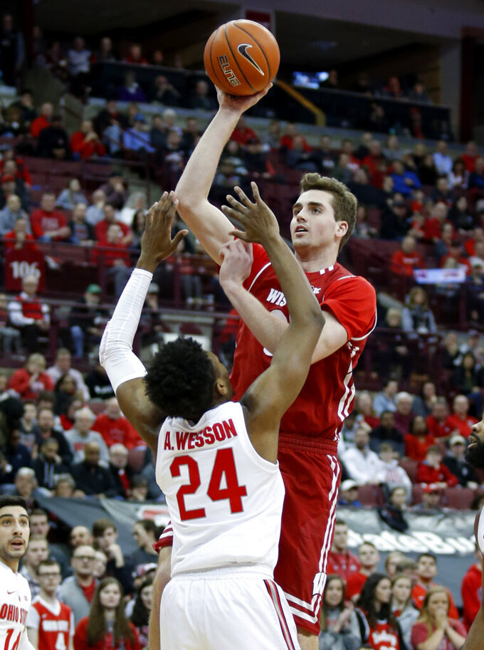 Wisconsin forward Nate Reuvers, right, goes up for a shot against Ohio State forward Andre Wesson during the first half of an NCAA college basketball game in Columbus, Ohio, Sunday, March 10, 2019. (AP Photo/Paul Vernon)