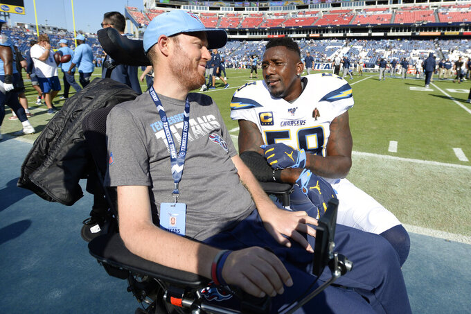 Los Angeles Chargers outside linebacker Thomas Davis (58) talks with former Tennessee Titans linebacker Tim Shaw before an NFL football game Sunday, Oct. 20, 2019, in Nashville, Tenn. Shaw was diagnosed in 2014 with ALS. (AP Photo/Mark Zaleski)