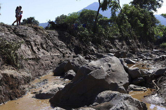 Women take pictures of an area destroyed by a deadly landslide in Nejapa, El Salvador, Friday, Oct. 30, 2020. The slide occurred Thursday night when earth from the upper part of the San Salvador volcano was set in motion, sweeping up trees and homes. (AP Photo/Salvador Melendez)