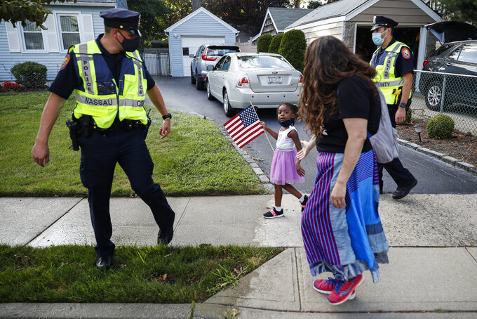FILE - This photo from Monday July 13, 2020, shows Nassau County Police officers walk alongside protesters participating in a Black Lives Matter march through a residential neighborhood calling for racial justice in Valley Stream, N.Y. Nassau County lawmakers are set to vote Monday, Aug. 2, 2021 on a proposal that would allow police officers to sue protesters and collect financial damages — a move civil rights activists say is payback for demonstrations after the police killing of George Floyd last year in Minneapolis. (AP Photo/John Minchillo, File)