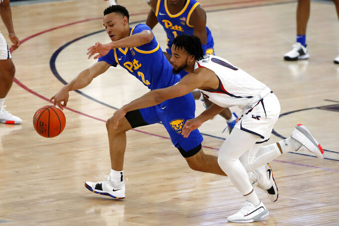 Pittsburgh's Trey McGowens (2) brings the ball up next to Robert Morris' Josh Williams during the first half of an NCAA college basketball game in Pittsburgh, Tuesday, Nov. 12, 2019. (AP Photo/Gene J. Puskar)