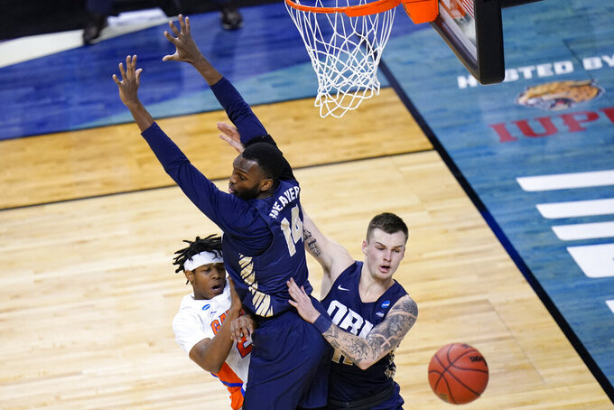 Florida guard Tyree Appleby, left, passes around Oral Roberts forward DeShang Weaver (14) and guard Carlos Jurgens, right, during the first half of a college basketball game in the second round of the NCAA tournament at Indiana Farmers Coliseum, Sunday, March 21, 2021 in Indianapolis. (AP Photo/AJ Mast)