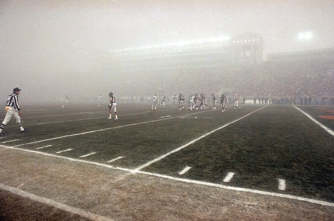 FILE - In this Dec. 31, 1988, file photo, lights shine through the fog during an NFL football playoff game between the Chicago Bears and the Philadelphia Eagles at Soldier Field in Chicago. Chicago's victory in the Fog Bowl 30 years ago is the only time the Bears have defeated the Eagles in three playoff meetings. The Bears get another chance when they host the Eagles in an NFC wild-card game. (AP Photo, File)