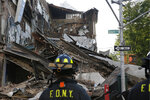 A firefighter looks at the rubble of a multistory building that collapsed Wednesday, July 1, 2020, in the Carroll Gardens neighborhood of the Brooklyn borough of New York. The multistory building, which had been shuttered during the coronavirus pandemic, housed a health club. Building inspectors had ordered a halt to some construction work at the location because of structural problems just three weeks before the collapse. (AP Photo/Kathy Willens)