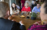 New Zealand Prime Minister Jacinda Ardern, left, talks with colleagues at a cafe in Auckland, New Zealand, Sunday, Oct. 18, 2020. Ardern has won a second term in office in an election landslide of historic proportions. (AP Photo/Mark Baker)