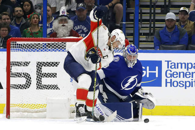 Florida Panthers center Aleksander Barkov (16) works for the puck in front of Tampa Bay Lightning goaltender Andrei Vasilevskiy (88) during the second period of an NHL hockey game Monday, Dec. 23, 2019, in Tampa, Fla. (AP Photo/Chris O'Meara)