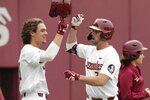 Florida State NCAA college baseball player Reese Albert, right, takes a bite of a cookie as he fist bumps teammate Elijah Cabell after Albert hit a home run against the Univ. of Maine, Friday Feb. 15, 2019, in Tallahassee, Fla. If all had gone as he hoped, Elijah Cabell and his Florida State teammates would be playing for the College World Series championship this week. Instead, Cabell treks to a ball field in his neighborhood in Winter Park, Florida, most days to work on his game in solitude.  (Alicia Devine/Tallahassee Democrat via AP)