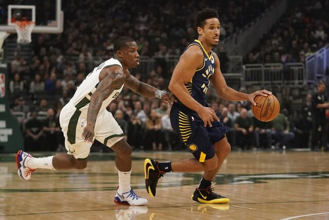 Indiana Pacers' Malcolm Brogdon drives past Milwaukee Bucks' Eric Bledsoe during the first half of an NBA basketball game Wednesday, March 4, 2020, in Milwaukee. (AP Photo/Morry Gash)