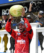 Ross Chastain holds a watermelon in victory lane after winning a NASCAR Truck Series auto race, Saturday, July 27, 2019, in Long Pond, Pa. (AP Photo/Derik Hamilton)