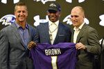 Baltimore Ravens NFL football first round draft pick Marquise Brown, center, stands with head coach John Harbaugh, left, and Executive Vice President/General Manager Eric DeCosta Friday, April 26, 2019, in Owings Mills, Md. (AP Photo/Gail Burton)
