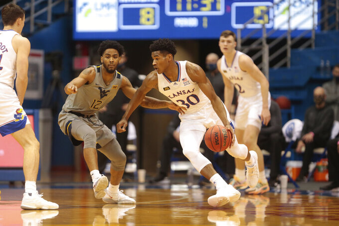 Kansas guard Ochai Agbaji maneuvers around West Virginia's Taz Sherman (12) during the first half of an NCAA college basketball game Tuesday, Dec. 22, 2020, in Lawrence, Kan. (Evert Nelson/The Topeka Capital-Journal via AP)