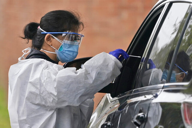 Medical personnel prepare to administer a COVID-19 swab at a drive-through testing site in Lawrence, N.Y., Wednesday, Oct. 21, 2020.  U.S. health officials are redefining what it means to have close contact with someone with COVID-19. On Wednesday, the CDC changed it to a total of 15 minutes or more, so briefer but repeated contacts that add up to 15 minutes now count.  (AP Photo/Seth Wenig)