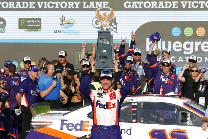 Denny Hamlin. center, holds up the winner's trophy after driving to victory in a NASCAR Cup Series auto race at ISM Raceway, Sunday, Nov. 10, 2019, in Avondale, Ariz. (AP Photo/Ralph Freso)