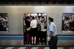 In this July 31, 2019, photo, a station attendant tells commuters to bring their feet inside an overcrowded train before the doors close during morning rush hours at Kiba Station in Tokyo. Tokyo has one of the most advanced public transport systems in the world, but with less than one year to go before the city hosts the 2020 Olympic Games, local governments, companies and commuters are bracing for unprecedented strain the events could put on rail transit and highways. (AP Photo/Jae C. Hong)