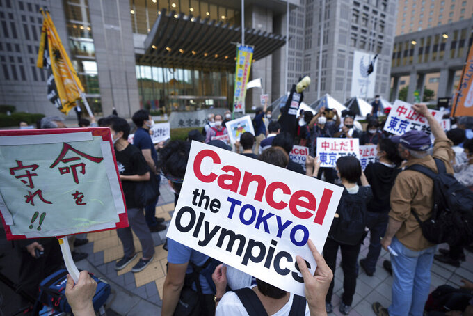 FILE - In this June 23, 2021, file photo, people against the 2020 Summer Olympics, gather to protest around the Tokyo Metropolitan Government building during a demonstration in Tokyo. (AP Photo/Eugene Hoshiko, File)