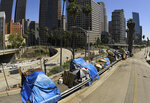FILE - This May 21, 2020, file photo shows a homeless encampment on Beaudry Avenue as traffic moves along Interstate 110 in downtown Los Angeles. Los Angeles is again considering a proposal to greatly restrict where homeless people may camp in public places around Los Angeles — rules that opponents say would criminalize homelessness. The City Council on Wednesday, Oct. 28, 2020, will debate changes to the city's code that would prevent people from sleeping within 500 feet of