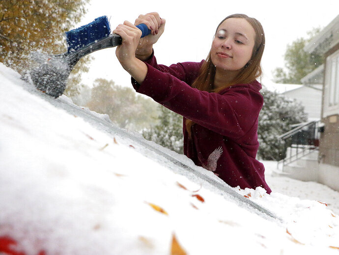 MaKenzie Gregory scrapes ice off her vehicle's front windshield as snow continues to fall in Scottsbluff, Neb., Thursday, Oct. 10, 2019. Gregory said she didn't know it was going to snow that much. (Lauren Brant/The Star-Herald via AP)