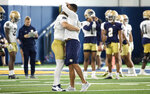 Notre Dame defensive coordinator Marcus Freeman and linebacker Bo Bauer (52) share a hug during Notre Dame Fall Camp on Saturday, Aug. 7, 2021, at Irish Athletics Center in South Bend, Ind. (John Mersits/South Bend Tribune via AP)