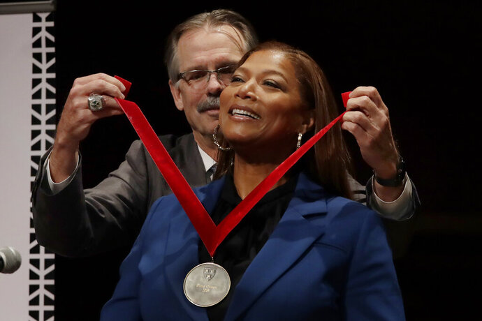 Music artist and actress Queen Latifah receives the W.E.B. Dubois Medal for her contributions to black history and culture from Glenn H. Hutchins during ceremonies at Harvard University, Tuesday, Oct. 22, 2019, in Cambridge, Mass. (AP Photo/Elise Amendola)