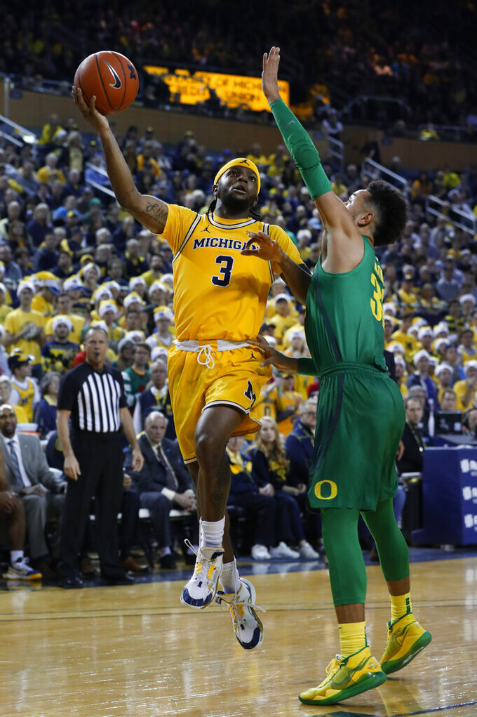 Michigan guard Zavier Simpson (3) drives on Oregon guard Anthony Mathis (32) in the second half of an NCAA college basketball game in Ann Arbor, Mich., Saturday, Dec. 14, 2019. (AP Photo/Paul Sancya)