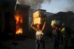 Vendors carry salvaged merchandise from the burned ruins of the Guerite Market that was engulfed in flames in Port-au-Prince, Haiti, early Tuesday, Jan. 14, 2020. (AP Photo/Dieu Nalio Chery)