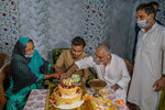 Haseeb Mushtaq, center, a Kashmiri groom along with his parents cut the cake during a henna ceremony of a wedding on the outskirts of Srinagar, Indian controlled Kashmir, Sunday, Sept. 13, 2020. The coronavirus pandemic has changed the way people celebrate weddings in Kashmir. The traditional week-long feasting , elaborate rituals and huge gatherings have given way to muted ceremonies with a limited number of close relatives attending. With restrictions in place and many weddings cancelled, the traditional wedding chefs have little or no work. The virus has drastically impacted the life and businesses in the region. (AP Photo/ Dar Yasin)