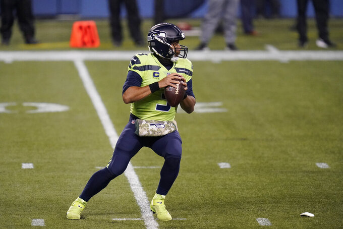 Seattle Seahawks quarterback Russell Wilson drops to pass during the first half of an NFL football game against the Arizona Cardinals, Thursday, Nov. 19, 2020, in Seattle. (AP Photo/Elaine Thompson)
