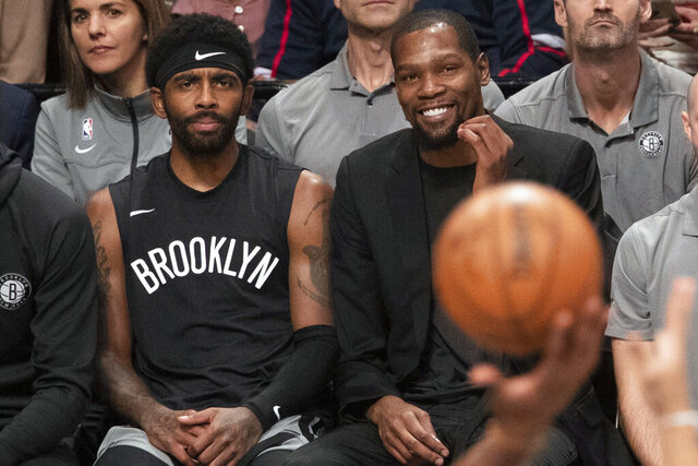 FILE - In this Nov. 1, 2019, file photo, Brooklyn Nets' Kyrie Irving, left, and Kevin Durant watch the game action from the bench during the second half of an NBA basketball game against the Houston Rockets in New York. With so much uncertainty around the NBA season, Brooklyn Nets general manager Sean Marks is no longer ruling Kevin Durant out for the season. Marks had repeatedly said he didn't expect Durant to play this season while recovering from Achilles tendon surgery, but he acknowledged Wednesday that everything is unknown now that the season is suspended because of the new coronavirus. Even Kyrie Irving, who had shoulder surgery on March 3, might be available if play stretched into the summer. (AP Photo/Mary Altaffer, File)