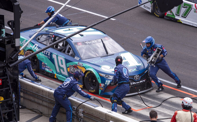 The pit crew of Martin Truex Jr. (19) work on the car during a pit stop during a NASCAR Cup Series auto race at Indianapolis Motor Speedway, Sunday, Aug. 15, 2021, in Indianapolis. (AP Photo/Doug McSchooler)