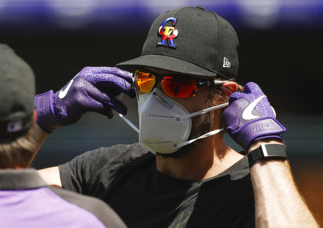 Colorado Rockies left fielder David Dahl puts on a face mask while taking part in drills as the team practiced Wednesday, July 8, 2020, in Denver. (AP Photo/David Zalubowski)