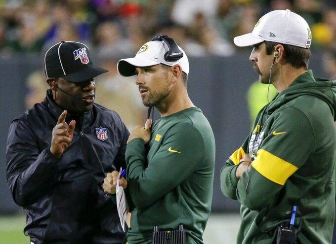 Green Bay Packers' Aaron Rodgers watches as head coach Matt LaFleur talks to an official during the first half of a preseason NFL football game against the Kansas City Chiefs Thursday, Aug. 29, 2019, in Green Bay, Wis. (AP Photo/Mike Roemer)