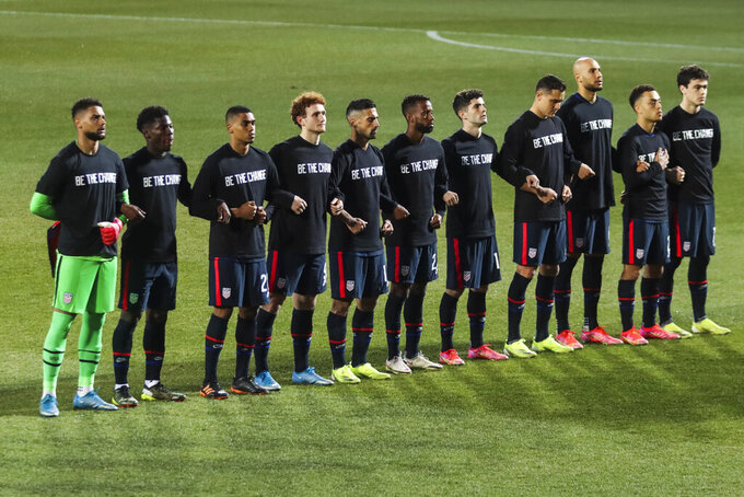 US players stand during the national anthem prior the international friendly soccer match between USA and Jamaica at SC Wiener Neustadt stadium in Wiener Neustadt, Austria, Thursday, March 25, 2021. (AP Photo/Ronald Zak)